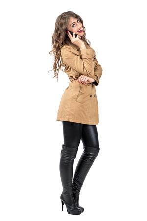 long pants: Happy smiling woman in autumn beige coat talking on the mobile phone looking at camera. Full body length portrait isolated over white studio background.