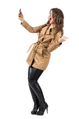 Opgewonden gelukkige vrouw die beige jas draagt met selfie met een mobiele telefoon. Full body lengte portret geïsoleerd over witte studio achtergrond.