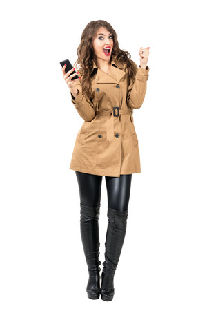 excited woman: Cheerful excited woman holding mobile phone with thumbs up gesture. Full body length portrait isolated over white studio background. Stock Photo