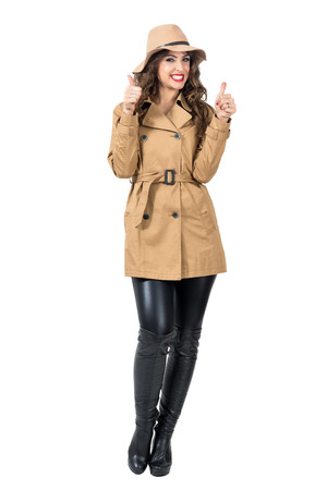 Excited cheerful woman wearing floppy hat and coat with thumbs up gesture. Full body length portrait isolated over white studio background.