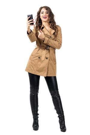 completos: belleza de la moda joven en ropa de otoño que sostienen el móvil de teléfono que toma la foto. la longitud del cuerpo Retrato completo aislado sobre fondo blanco del estudio.