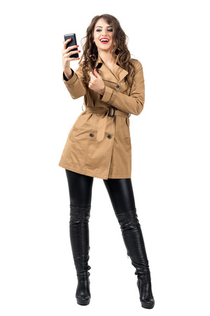 Young fashion beauty in autumn clothes holding mobile phone taking photo. Full body length portrait isolated over white studio background.