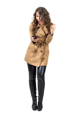 excited woman: Ecstatic young woman wearing coat looking at mobile phone. Full body length portrait isolated over white studio background.