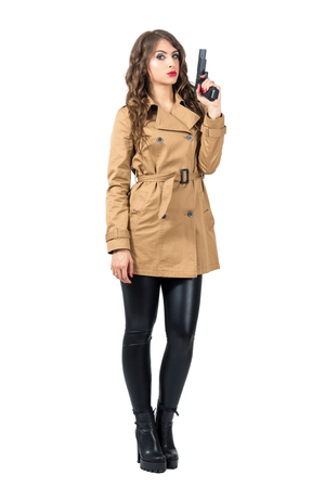 femme fatale: Serious female spy wearing beige coat holding gun looking at camera. Full body length portrait isolated over white studio background.