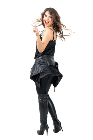 Excited happy woman with thumbs up gesture turns at camera with stopped hair motion. Full body length portrait isolated over white studio background.