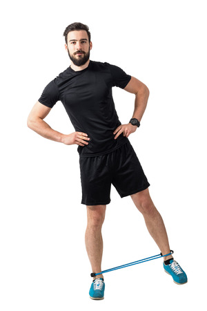elastic: Fitness athlete doing side leg-lifts exercise with resistance bands.  Full body length isolated over white studio background.
