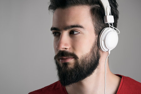 man with beard: Closeup profile view of young handsome bearded man with headphones looking away over gray background Stock Photo