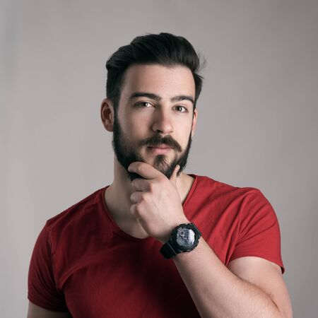 beard man: Puzzled young man stroking touching beard looking at camera over gray background Stock Photo