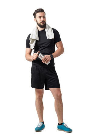 Young bearded male athlete with towel holding plastic water bottle. Full body length isolated over white studio background.