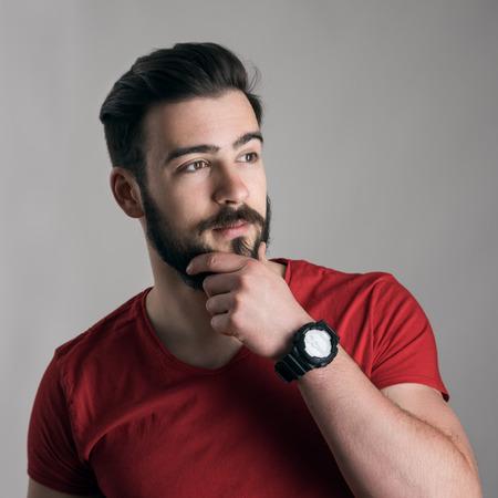 uomo rosso: Raffreddare pensiero giovane uomo con la mano sul mento tocca la barba cerca di distanza su sfondo grigio