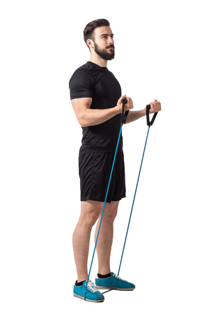 Young fitness athlete doing bicep curl arms exercise with resistance bands.  Full body length isolated over white studio background.
