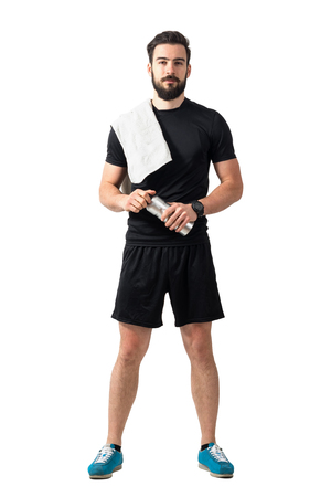 Jonge zelfvertrouwde atleet met handdoek en fles kijken naar camera. Volledige lichaamslengte geïsoleerd over witte studio achtergrond.