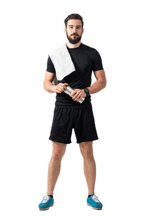 Jonge zelfvertrouwde atleet met handdoek en fles kijken naar camera. Volledige lichaamslengte geïsoleerd over witte studio achtergrond. Stockfoto - 59122122