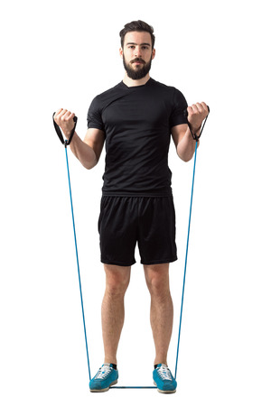 frontal: Front view of young fitness model doing bicep curls with elastic bands.  Full body length isolated over white studio background.