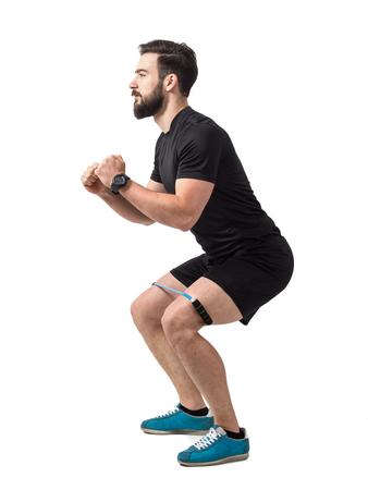 hombre deportista: Atleta joven en cuclillas ejercicio con banda de resistencia alrededor de las piernas. longitud de cuerpo completo aislado sobre fondo blanco del estudio.
