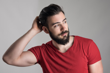 bearded: Young handsome bearded man in red t-shirt scratching head looking away over gray background