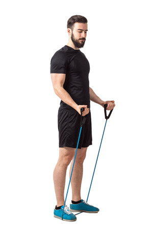 elastic band: Fit young bearded athlete preparing for bicep muscle arms exercise.  Full body length isolated over white studio background. Stock Photo
