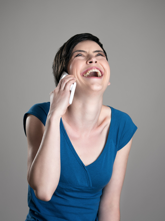 tilted: Spontaneous laughing short hair woman while talking on the mobile phone looking up