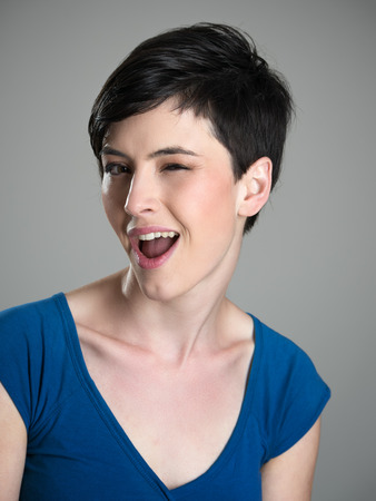 woman short hair: Portrait of young short hair cute woman winking at camera with open mouth