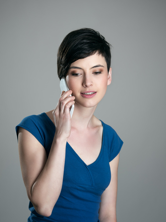 feminine beauty: Feminine gorgeous short hair beauty talking on the cellphone looking down