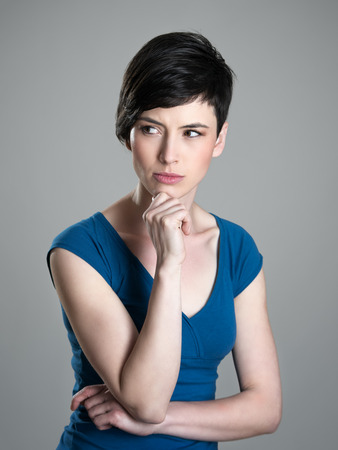 Serious suspicious or worried young short hair woman looking away with hand on her chin