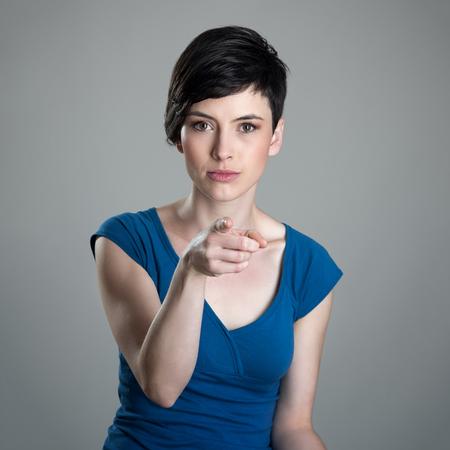 blaming: Young short hair woman pointing finger at camera accusing or blaming you