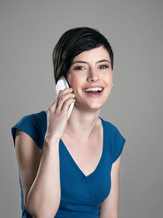 ojos marrones: Feliz mujer de pelo corto que habla en el teléfono móvil con una sonrisa con dientes mirando a la cámara