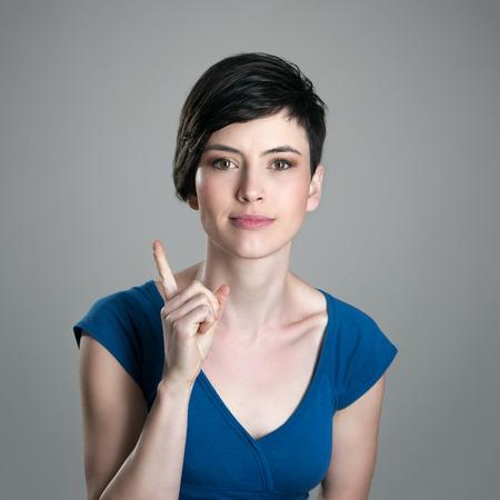 cabeza femenina: mujer joven de pelo corto regañando dedo mirando a la cámara sobre fondo gris de estudio sonriendo