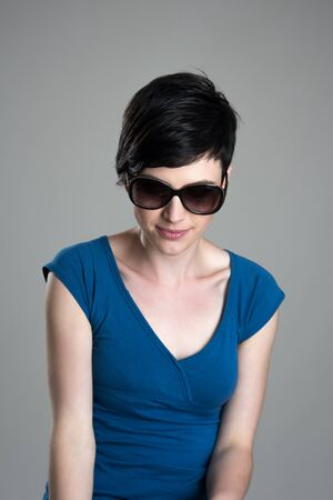 feminine beauty: Feminine short hair beauty wearing sunglasses looking down Stock Photo