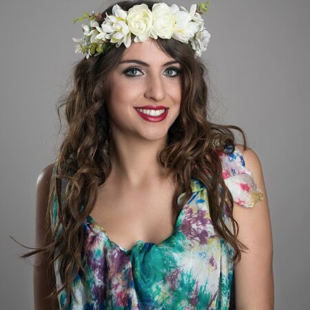 toothy smile: Beautiful happy fantasy girl with flowers in her head posing at camera with toothy smile Stock Photo