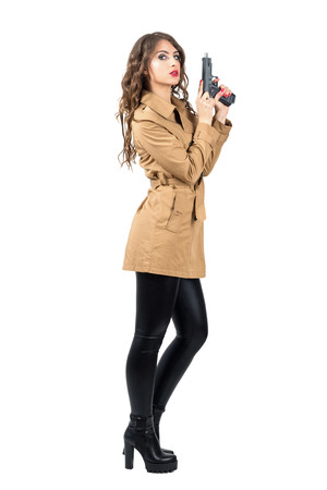 femme fatale: Sexy female spy wearing coat cocking handgun side view. Full body length portrait isolated over white studio background Stock Photo