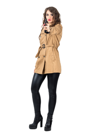 femme fatale: Sexy dangerous wavy hair spy wearing coat aiming weapon at camera. Full body length portrait isolated over white studio background Stock Photo
