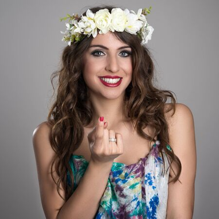to beckon: Portrait of young fairy girl with flower wreath smiling with inviting finger gesture over gray studio background