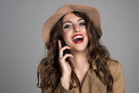 laughing face: Attractive beauty wearing hat and autumn clothes laughing while talking on the mobile phone over gray studio background