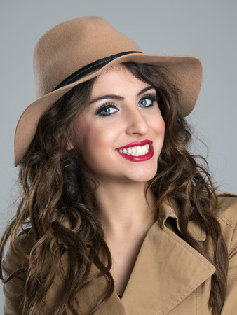 toothy smile: Close up portrait of young beauty with red lips and white toothy smile wearing hat over gray studio background