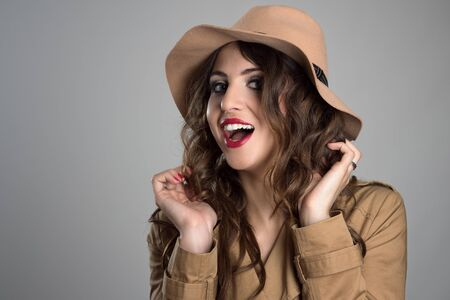 glamour hair: Glamour woman wearing hat adjusting and touching her hair looking at camera over gray studio background