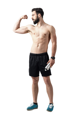 male body: Strong fit young shirtless man flexing bicep muscle and holding water bottle. Full body length portrait isolated over white studio background. Stock Photo