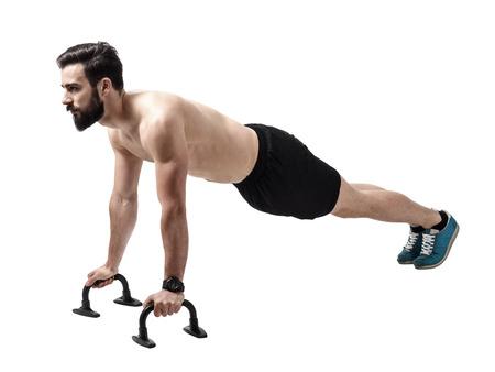 pushup: Shirtless muscular athlete doing push-up on push up bars. Full body length portrait isolated over white studio background. Stock Photo