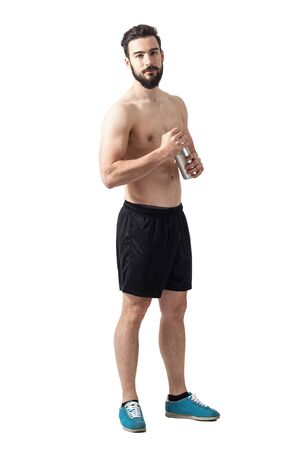 Serious focused fit shirtless athlete holding water bottle looking at camera. Full body length portrait isolated over white studio background.