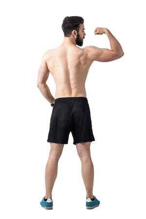 muscle toning: Rear view of young fit athlete flexing arm muscles. Full body length portrait isolated over white studio background.