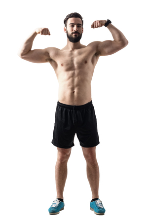 Front view of young bearded fit athlete flexing muscles. Full body length portrait isolated over white studio background.