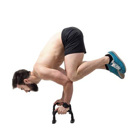 barra de bar: El pino fuertes atleta sin camisa equilibrio sobre empujan hacia arriba bares. la longitud del cuerpo Retrato completo aislado sobre fondo blanco del estudio. Foto de archivo