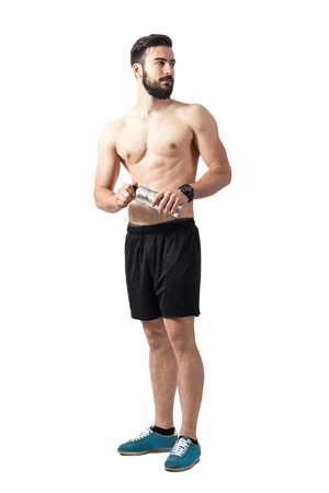 turn away: Young fit muscular athlete holding water bottle turning back looking away. Full body length portrait isolated over white studio background.