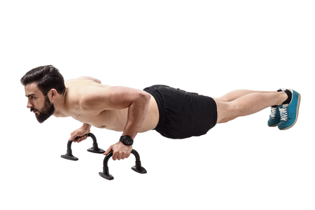 handle bars: Side view of shirtless fit athlete workout on push up handles. Full body length portrait isolated over white studio background.