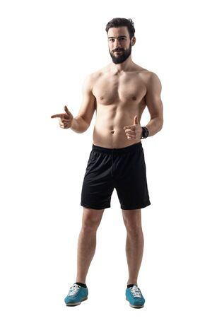 male body: Shirtless fit young athlete pointing finger and smiling at camera. Full body length portrait isolated over white studio background.