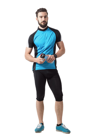 Bearded young adult cyclist with water bottle looking at camera. Full body length portrait isolated over white studio background.
