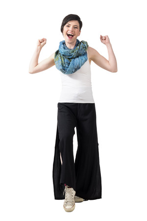 legs wide open: Excited winning young girl wearing loose trousers and colorful shawl with clenched fists. Full body length portrait isolated over white studio background.