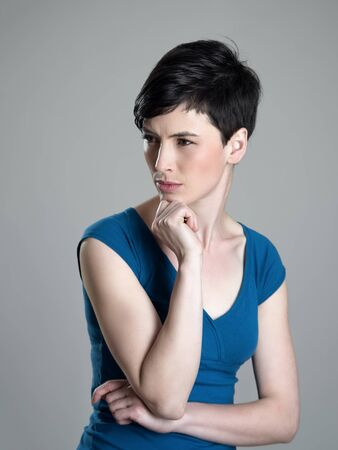 beauty eyes: Unhappy short hair beauty looking away squinting eyes over gray studio background