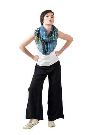 Short hair fashion model with colorful shawl and loose wide trousers posing with arms on her hips. Full body length portrait isolated over white studio background.