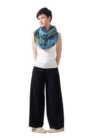 awkward: Shy bashful young short hair woman in wide pants in awkward leg pose. Full body length portrait isolated over white studio background.